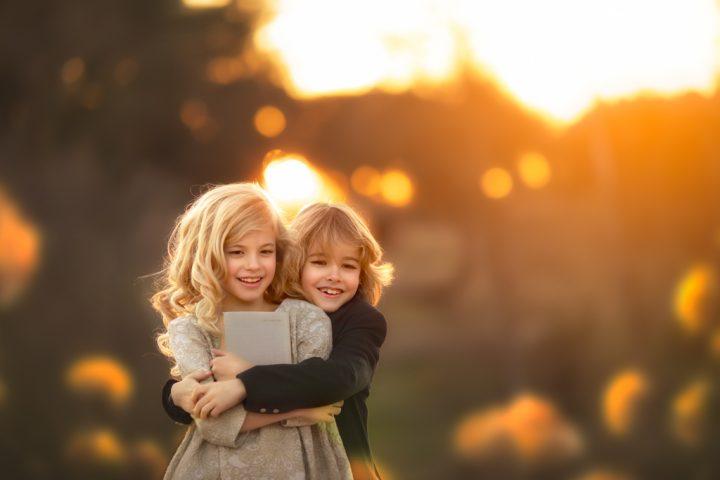 una niña rubia con hermano en traje de comuniones en reportaje fotográfico en exteriores