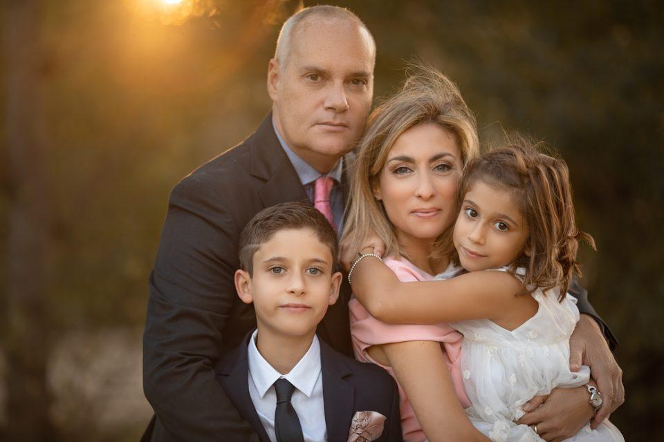 una foto familiar de reportaje de primera comunión en exteriores con una luz del atardecer