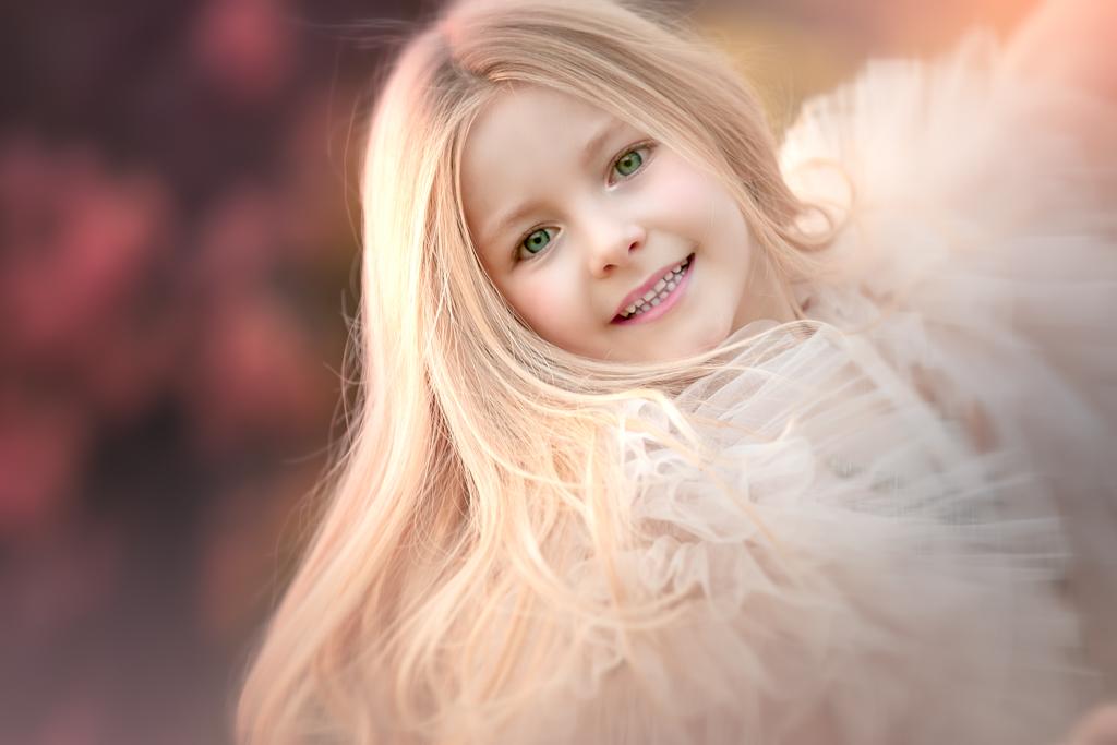 una niña rubia en traje de comunión en un reportaje fotografico en exteriores