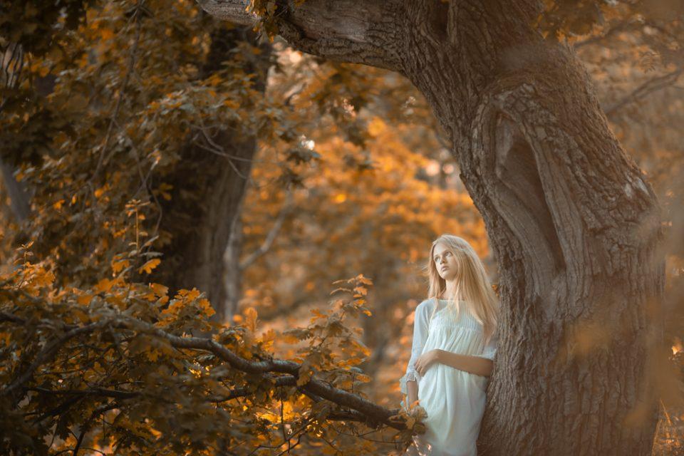 foto de niña con vestido blanco de comunión sentada en un árbol