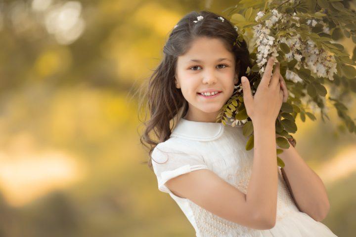 foto de niña en vestido de primera comunión en el campo al atardecer