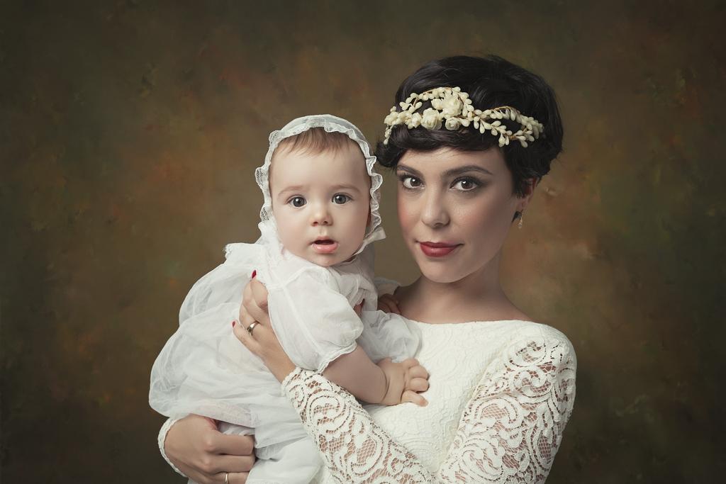 foto de mujer en vestido de boda y bebe en traje de bautizo