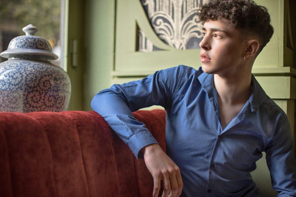 foto de un hombre joven en camisa azul sentado en una mesa mirando por la ventana