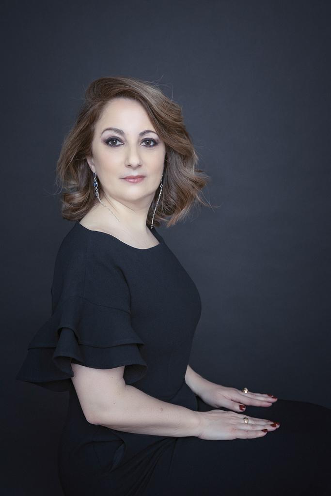 fotografia de mujer de personal branding y corporativa en traje negro y fondo negro