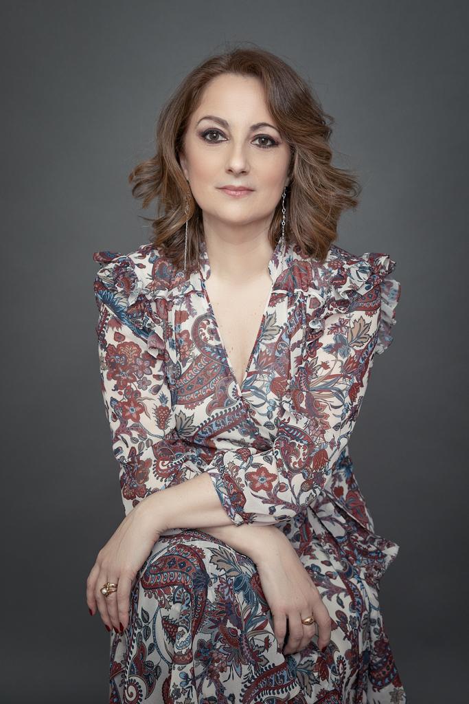 fotografia de mujer de personal branding y corporativa en traje gris y fondo gris