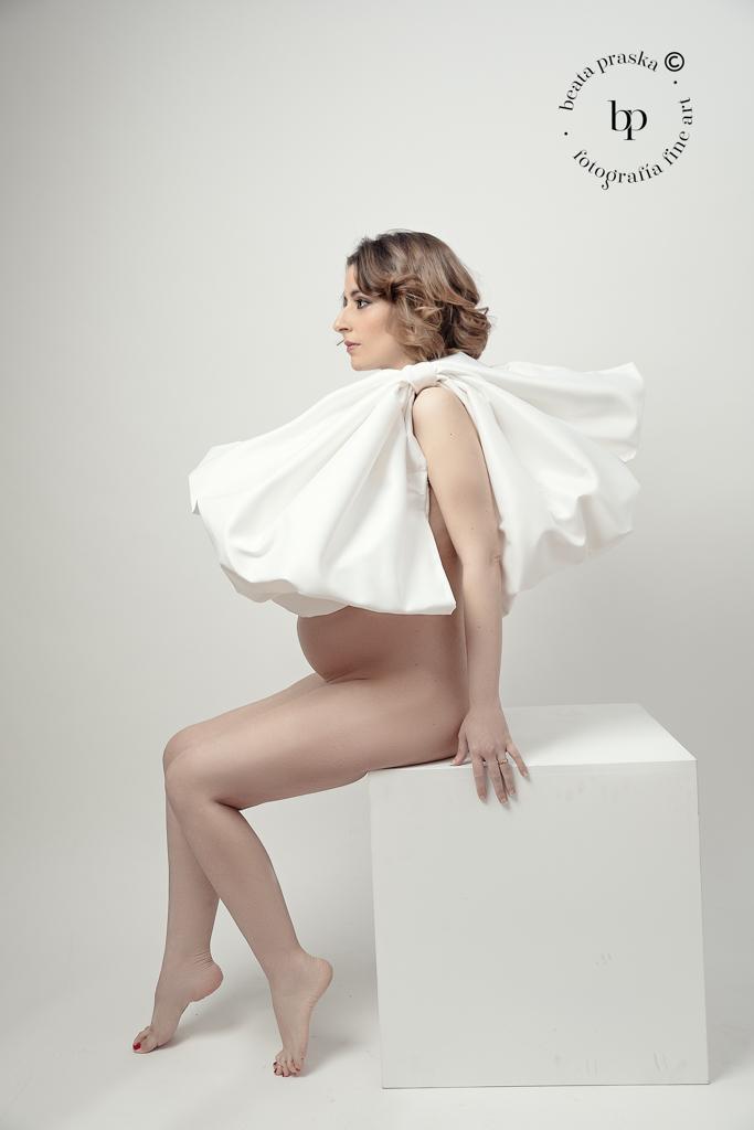 mujer embarazada con lazo blanco en estudio de Beata praska fotografia