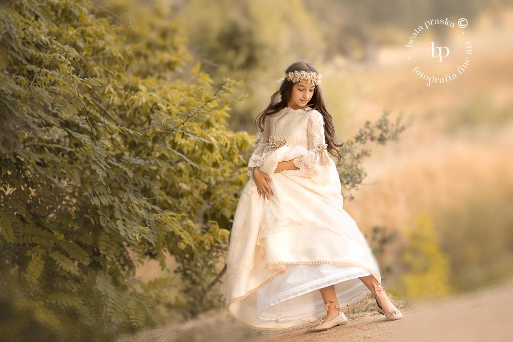 una niña en traje de comuniones fotografiada en exteriores por Beata Praska