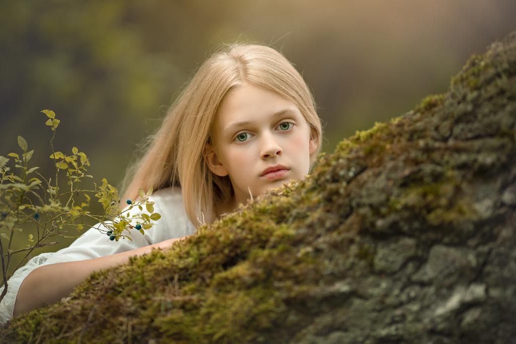 foto de niña rubia con ojos azules en vestido blanco de primera comunión apoyada en un árbol