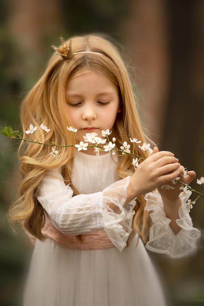 foto de niña en vestido blanco de primera comunión con flores blancos