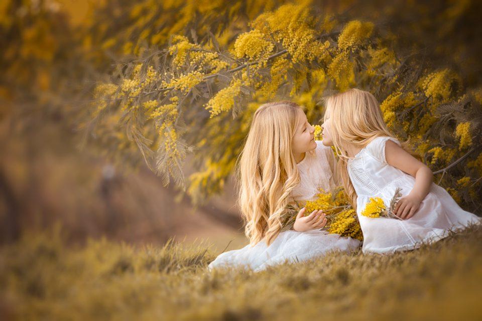 a foto de hermanas en vestido blanco en sesion fotografica de primera comunión en exteriores