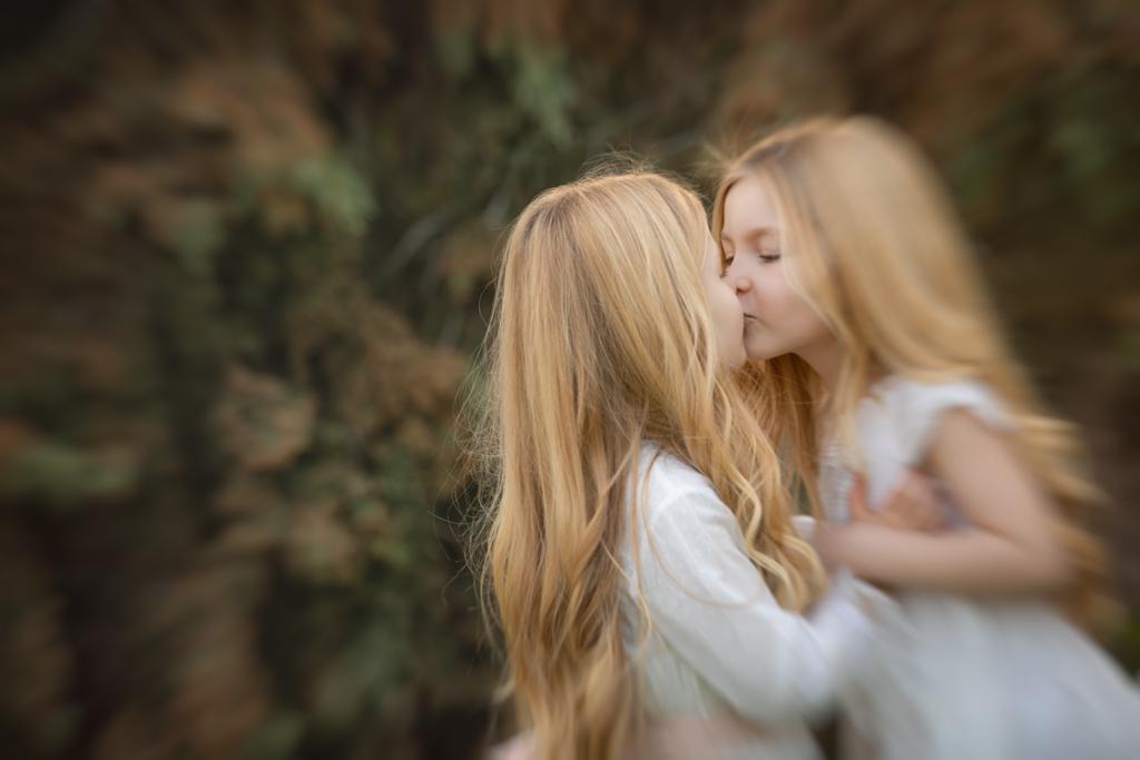 foto de hermanas en vestidos de comunión dándose un beso