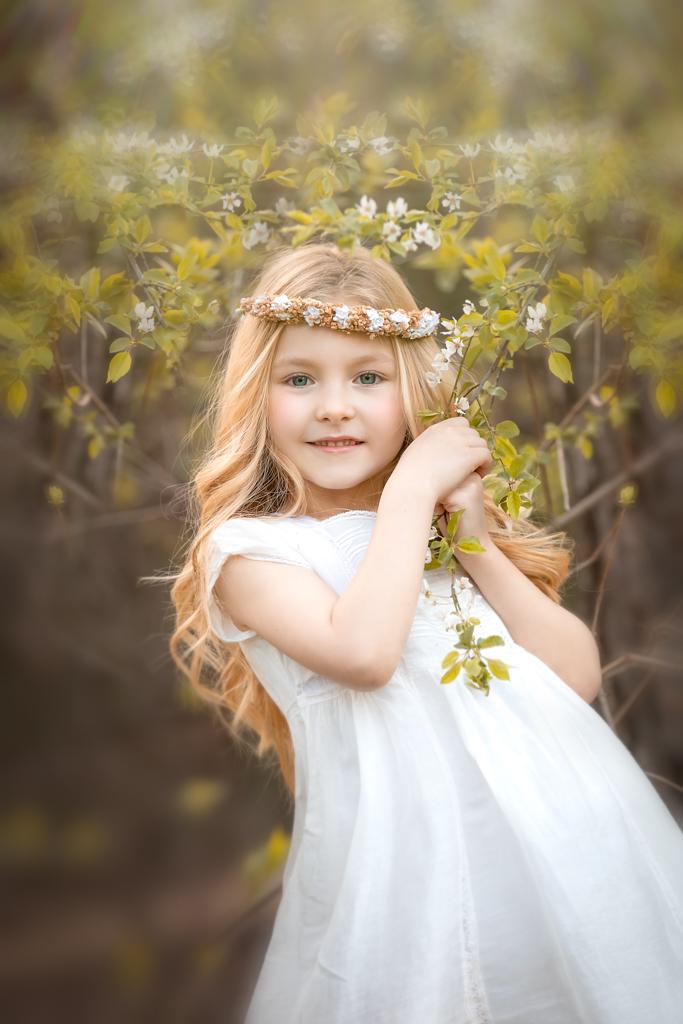 una foto de ninia rubia en vestido blanco en sesion fotografica de primera comunión en exteriores