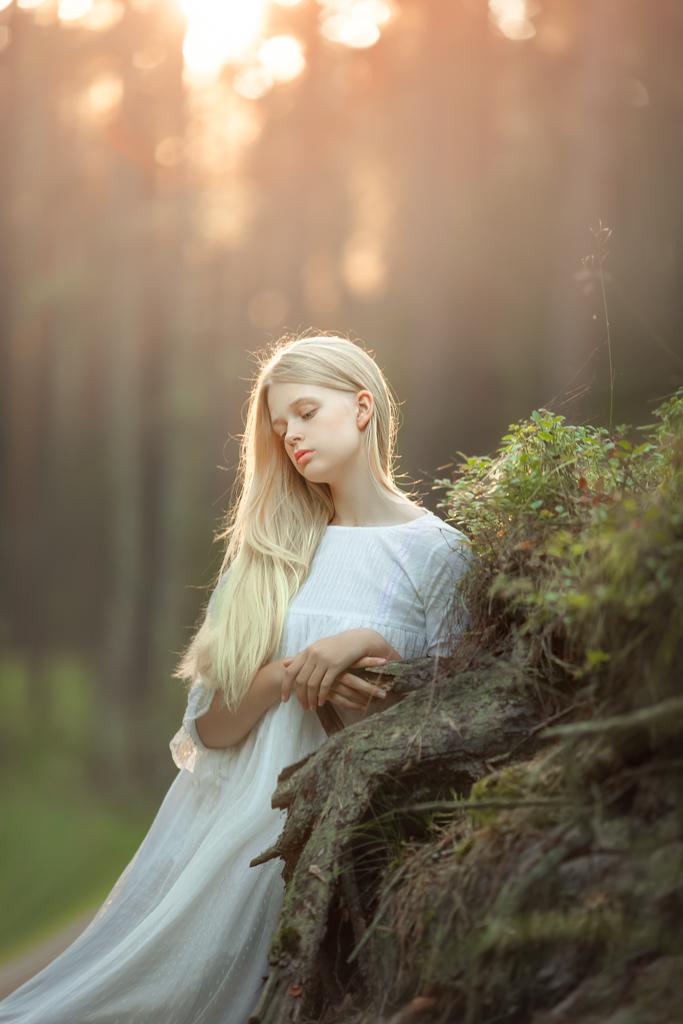 imagen de niña rubia con pelo largo y vestido blanco de primera comunión en una sesion de fotos en exteriores